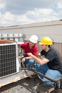 Commercial HVAC technichians in Greenville, SC examining a rooftop air conditioning unit.